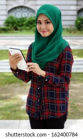 College muslim girl playing cellphone or tablet