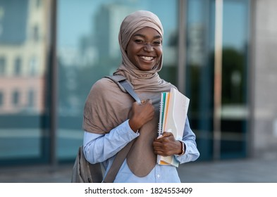 College Scholarships for Muslim Students. Happy Black Islamic Woman With Backpack And Workbooks Posing Outdoors At Campus, Resting After Classes, Wearing Hijab, Looking And Smiling At Camera