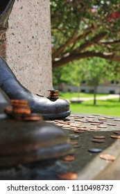 College Station, Texas / USA - August 19, 2013:  Pennies placed on the boot of the Sul Ross statue at Texas A&M University for luck during final exams.
