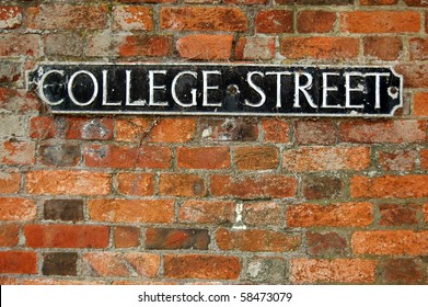 College Street roadsign An old, cast iron road sign for 'college street' on a warm orange brick wall.  Winchester, Hampshire