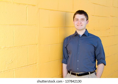 A college student business professional is photographed outside with natural light to create a portrait of a person wearing a grey shirt looking confident.
