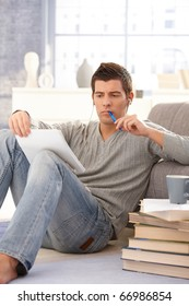 College student concentrating on studying sitting on living room floor with books and notes and pen.?