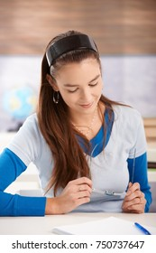 College student girl sitting at desk in classroom learning, looking down, smiling.