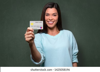 College student graduate excited and hopeful holding new credit card, entrepreneur, with blackboard background