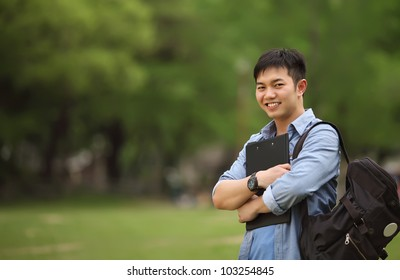 college student holding book on the park