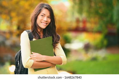 College student holding books walking on campus going to class smiling. Young smiling multiracial Asian woman girl with bag outdoor portrait.
