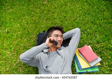 college student lying on a grass use mobile phone with book, ,bag at campus