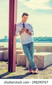 College Student in New York. Wearing white shirt, jeans, sneakers, a young guy standing against pole by Hudson River, looking down, checking messages on his mobile phone. Instagram filtered effect.