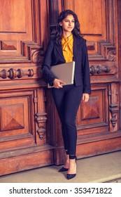 College Student in New York. Wearing black blazer, orange undershirt, pants, heels, carrying laptop computer, East Indian American business woman standing by vintage office doorway. Instagram effect.