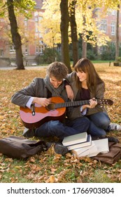 College student playing guitar for girlfriend on campus