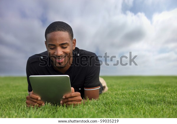 College Student Reading Outdoors Lying in the Grass