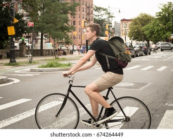 College student riding bike crossing the crosswalk in the city, photographed in Brooklyn, NY in July 2017