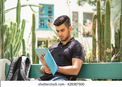 College student sitting on a bench, looking at his tablet computer