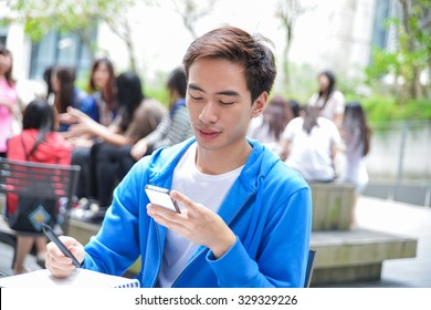 college student sitting use mobile phone in her hand at campus