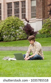 College student studying using laptop computer and with earbuds on university campus