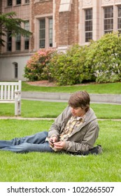 College student using listening to digital music audio device MP3 player with earbuds on university campus. Vertical image with copy space.