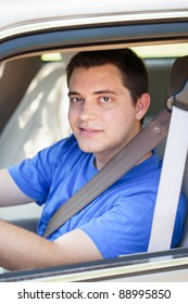 College student wearing seat belt in the car behind the wheel
