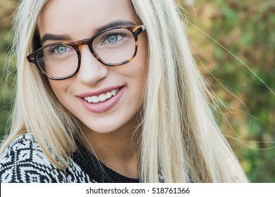 college student, a young woman, blonde, glasses, outdoors in the park