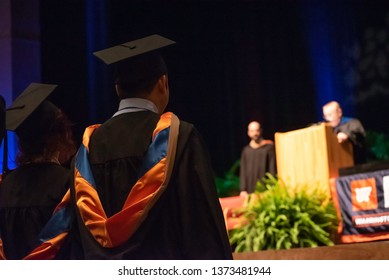 College students dressed in cap and gowns listen to a speech during a graduation ceremony.
