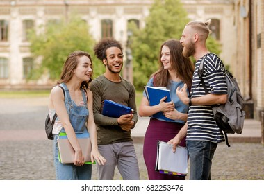 College students going to classes, talking and laughing. Friends meeting in campus before classes.