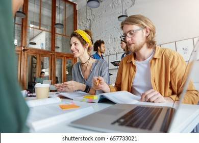College students sitting at table preparing for classes using books, notebooks and laptop. Hipster clever male in glasses sitting near his groupmate making some notes and drinking coffee together