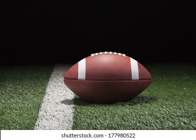 College style football on grass field and stripe at night low angle