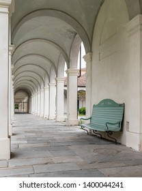 Collegno, Piedmont, Italy - May 17, 2019: Empty bench beneath the arcades of the Royal Charterhouse, a monastery built by Savoy in 17th century, turned into psychiatric hospital in 19th century.