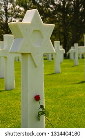 COLLEVILLE-SUR-MER, FRANCE - July 2, 2015: American war cemetery at Omaha Beach. Jewish cross with rose flower.