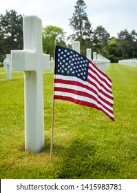 Colleville-sur-Mer / Normandie / France -June 6 -2012: A single war grave cross with American Flag at The Normandy American Cemetery and Memorial.