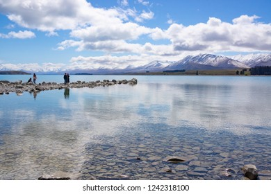 COLLINGWOOD, NEW ZEALAND - OCTOBER 5; Family four Asian tourists photographing scenery and enjoying waters edge and great views October 5 2018 Collingwood New Zealand