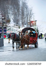 COLLINGWOOD, ON, CANADA - DECEMBER 17, 2018: Blue Mountain Village in winter day. Horse drawn carriage and tourists enjoy the winter village, Ontario, Canada - Image