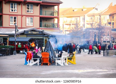COLLINGWOOD, ON, CANADA - DECEMBER 17, 2018: Blue Mountain Village in snowy winter day. People sit round a bonfire, Ontario, Canada - Image