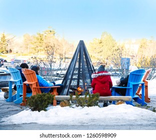COLLINGWOOD, ON, CANADA - DECEMBER 17, 2018: Blue Mountain Village in snowy winter day. People sit round a bonfire, Ontario, Canada