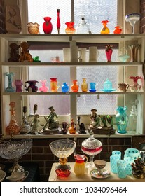 Collinsville, Connecticut, USA, February 26, 2018: colored glass objects on shelves in front of a window in an antique store