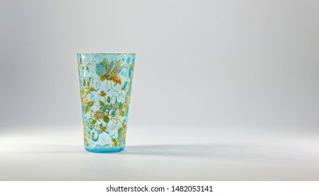 Colliston, Scotland - 17th July 2017: A 17th Century, Pale blue Glass Vase, embellished with an enamel of Flowers, leaves and Honey Bee's standing against a neutral background.
