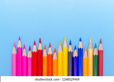 Collor wooden pencils in row isolated on bluebackground. Top view with copy space.