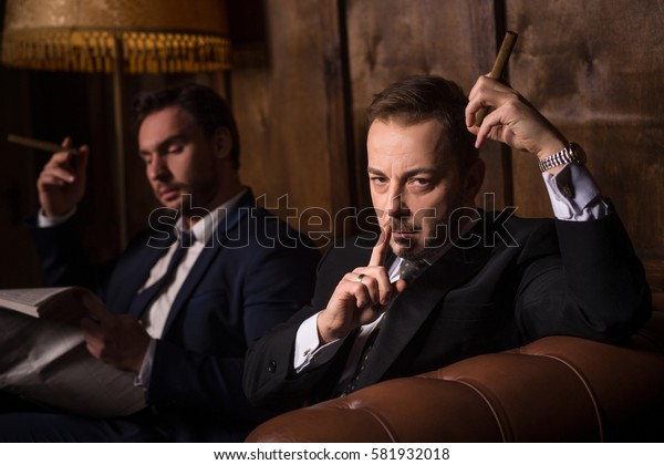 Collusion in business and global conspiracy between two successful businessmen while they are spending time in men's club and solving global problems.