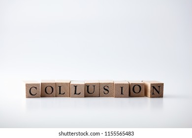 COLLUSION in wooden stamp blocks. Isolated on neutral white background.