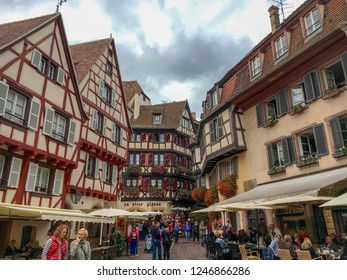 Colmar, France - 1. October 2016. Panorama of the central street in Colmar, facades of traditional half-timbered houses, flower decoration. Tourists in the historical district of the town.