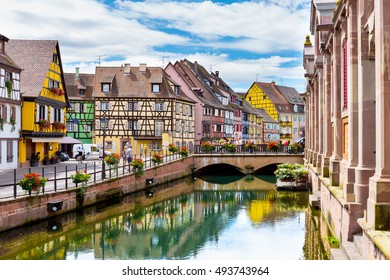 COLMAR, FRANCE AUGUST 03, 2016. Flowers decoration and typical architecture for Alsace region. Bridge over the river.