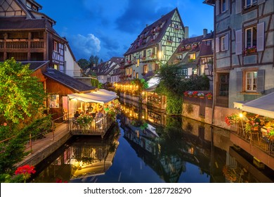 Colmar, France. Half-timbered houses and verandas of restaurants reflecting in the water at dusk in Petite Venise area