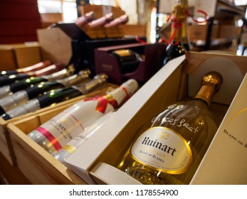COLMAR, FRANCE - MAY 1, 2018: Wide closeup of multiple bottles of Champagne from Ruinart, Moet and Chandon, aged in crates at a local wine store. Alsace Wine Route. Travel and tourism