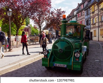 COLMAR, FRANCE - MAY 1, 2018: Wide view of a green mini-train tour driving through Little Venice downtown. Travel and attractions.