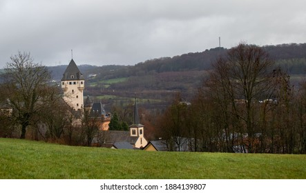 """Colmar-Berg, Luxembourg -12.28.2020: The tower of Berg Castle (Le château Berg or Schlass Bierg), and parts of the local church in Colmar-Berg, seen from on top of a green hillside."""