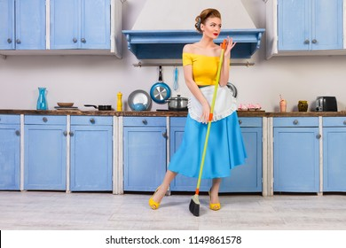 Colofrul retro / pin up girl woman female / housewife wearing colorful top, skirt and white apron holding mop and cleaning floor in the kitchen with blue cabinets and utensils. Housework concept