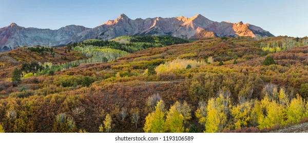 The coloful Autumn tableau seen from the Dallas Divide before sunrise on a crisp morning in the San Juan Mountains of Colorado.