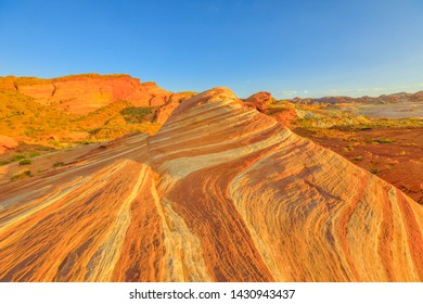 The coloful striped landscape at sunset of Fire Wave Trail at Valley of Fire State Park in Nevada, United States in Mojave desert. Fire Wave is one of the most iconic formations at Valley of Fire.