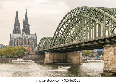 Cologne Beautiful Panorama Aerial View Jet Boat Cruise Rhine River under Landmark Hohenzollern Bridge with Cologne Cathedral under golden sky in summer evening sunset, Germany