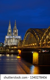 Cologne Cathedral and Hohenzollern Bridge during the blue hour in portrait format.