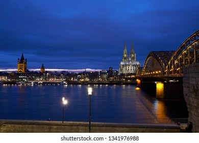 Cologne Cathedral, Hohenzollern Bridge Panorama, view of the old town of Cologne during the golden hour. Royal blue sky.